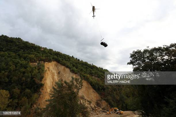 TOPSHOT A helicopter carries a vehicle during a winching operation after a landslide cut the road leading to the village of Sospel on October 17...