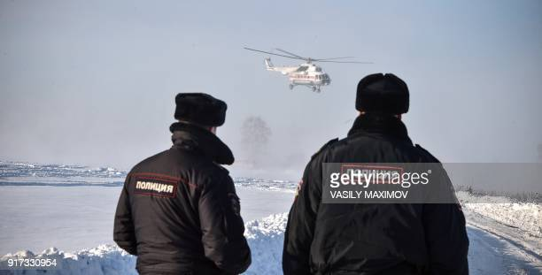 A helicopter carries away the bodies of the victims as Russian Emergency Ministry rescuers work at the site of a plane crash which occured the day...