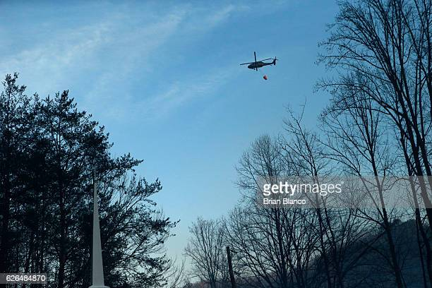 A helicopter carrying a bucket of water flies over the Banner Missionary Baptist Church as crews work a wildfire November 29 2016 in Gatlinburg...