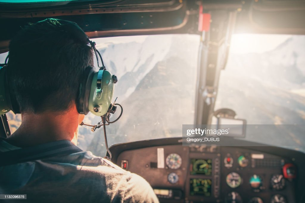 Helicopter cockpit with rear view of unrecognizable men co-pilot flying over Mont Blanc massif in French Alps mountains at sunset : Stock Photo