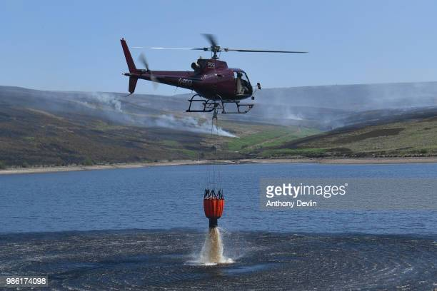 A helicopter collects water from Swineshaw reservoir in Stalybridge as wildfires continue to burn on the moors on June 28 2018 in Stalybridge England...