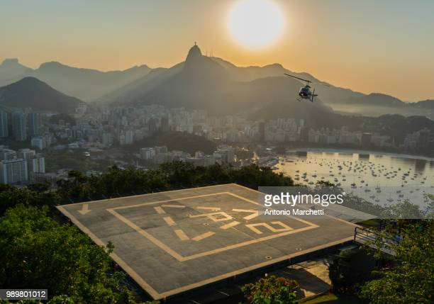 a helicopter coming in to land on sugarloaf mountain, rio de janeiro, brazil. - helipad stock photos and pictures