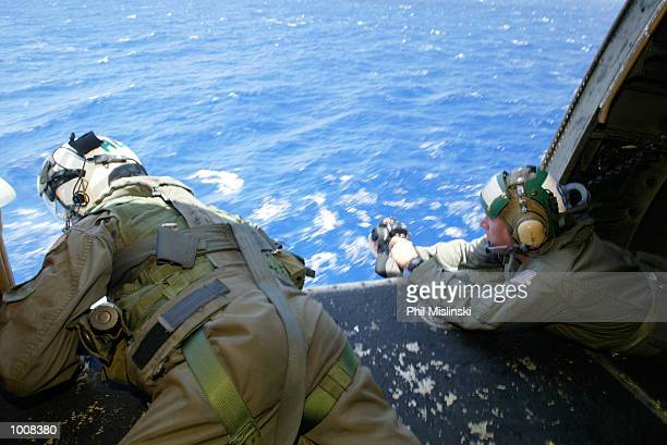 Helicopter crew chief Randall Elkins monitors a landing aboard the USS Lake Erie during the RIMPAC excercise operations July 11, 2002 near Oahu,...