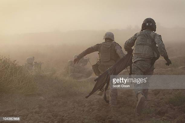 Helicopter crew chief Thomas Burns of Orange City FL and a U.S. Marne run to help a severely wounded Marine September 23, 2010 near Marja,...