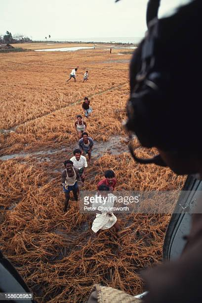 A helicopter crew member drops food to villagers in a remote region of Bangladesh as they reach up for the emergency supplies As a result of one of...