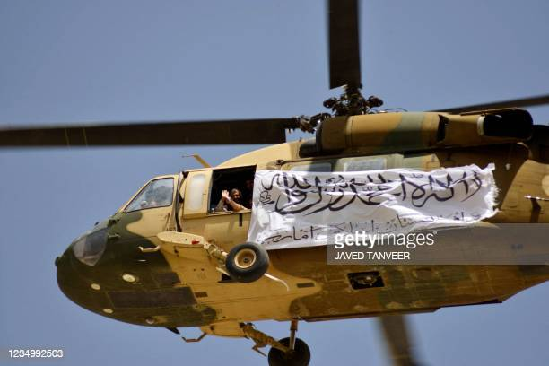 Helicopter displaying a Taliban flag flies above Taliban supporters gathered to celebrate the US withdrawal of all its troops out of Afghanistan, in...