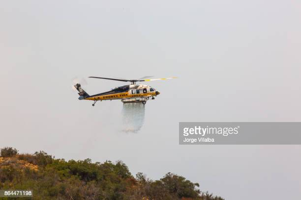 helicopter doing drops of water on the la tuna wildfire in los angeles - helicopter photos stock pictures, royalty-free photos & images
