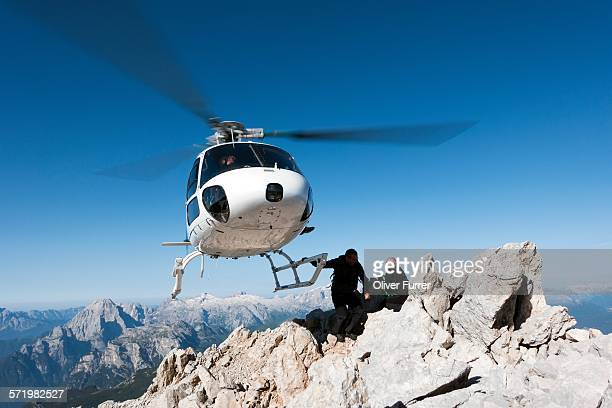 helicopter dropping base jumpers on mountain, dolomites, italy - hovering stock pictures, royalty-free photos & images