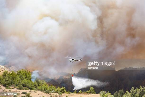 Helicopter dropping water for fire fighting