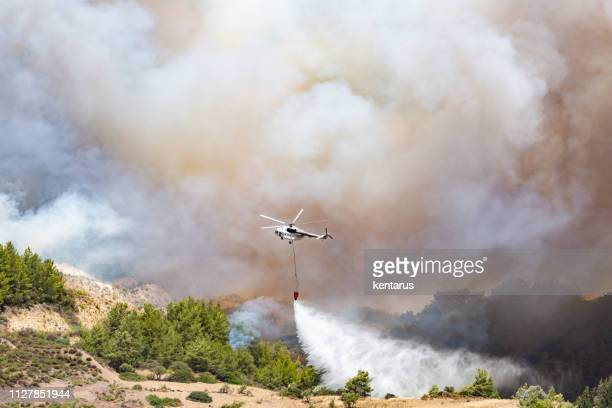 helicopter dropping water for fire fighting - smoking crack stock photos and pictures