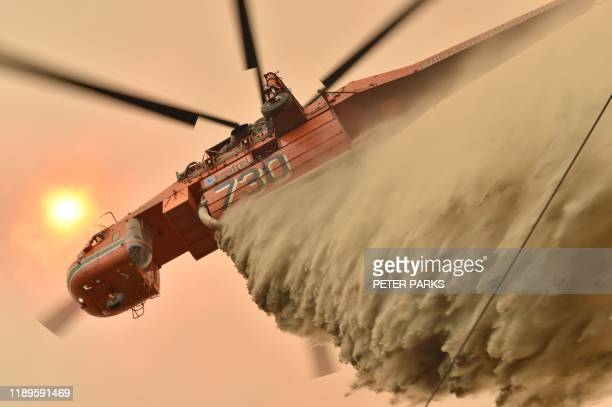 TOPSHOT A helicopter drops fire retardent to protect a property in Balmoral 150 kilometres southwest of Sydney on December 19 2019 A state of...