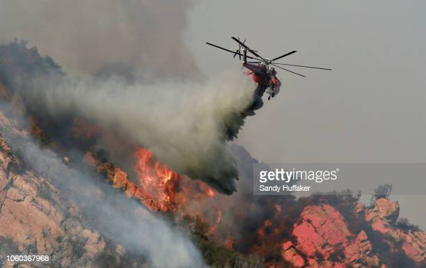 A helicopter drops flame retardant on a wildfire on November 10 2018 in Malibu California The Woolsey fire has burned over 70000 acres and has...