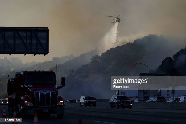 Helicopter drops water during a brush fire as vehicles drive in traffic on the 405 freeway through the Sepulveda Pass in Los Angeles, California,...