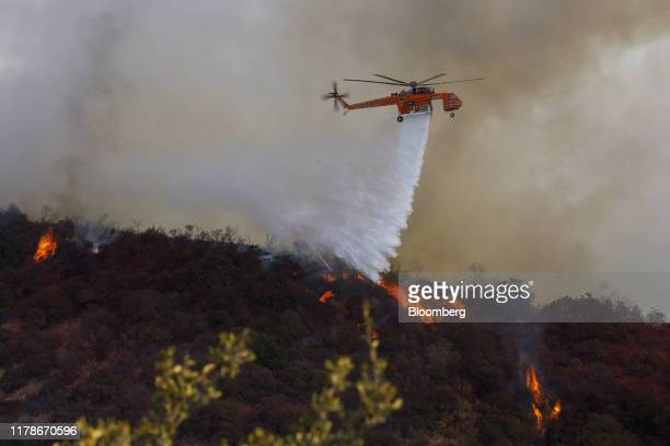 A helicopter drops water during a brush fire in Los Angeles California US on Monday Oct 28 2019 A fastmoving brush fire known as the Getty Fire has...
