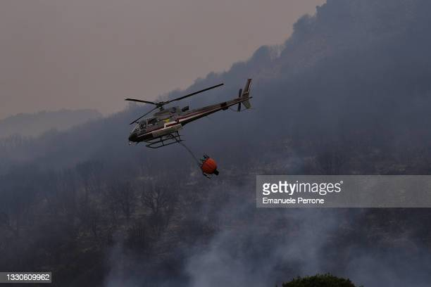 Helicopter drops water on a blaze that has destroyed thousands of hectares of land on July 25, 2021 in the province of Oristano in Sardinia, Italy....