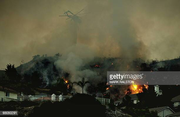 A helicopter drops water on a fire as it comes close to houses in the suburb of Glendale on the outskirts of Los Angeles city on September 1 2009 A...