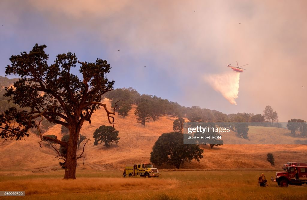 TOPSHOT - A helicopter drops water on a hillside as firefighters scramble to get control as flames from the Pawnee fire near Clearlake Oaks, California on July 1, 2018. - More than 30,000 acres have burned in multiple fires throughout the region.