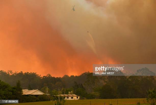 Helicopter drops water on a homestead as bushfires impact on farmland near the small town of Nana Glen, some 600kms north of Sydney on November 12,...