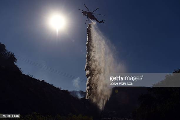 TOPSHOT A helicopter drops water on a hot spot in Keenbrook California on August 18 2016 The Blue Cut Fire has charred more than 35000 acres causing...