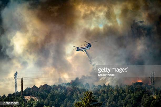 a helicopter drops water on a wild fire. - natural disaster stock pictures, royalty-free photos & images