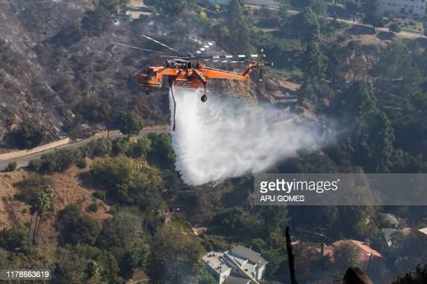 A helicopter drops water on houses as the Getty fire burns in the Brentwood area California on October 28 2019 A wildfire broke out early Monday near...