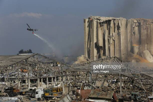 A helicopter drops water on smoldering buildings in the city's port destroyed by an explosion a day earlier on August 5 2020 in Beirut Lebanon As of...