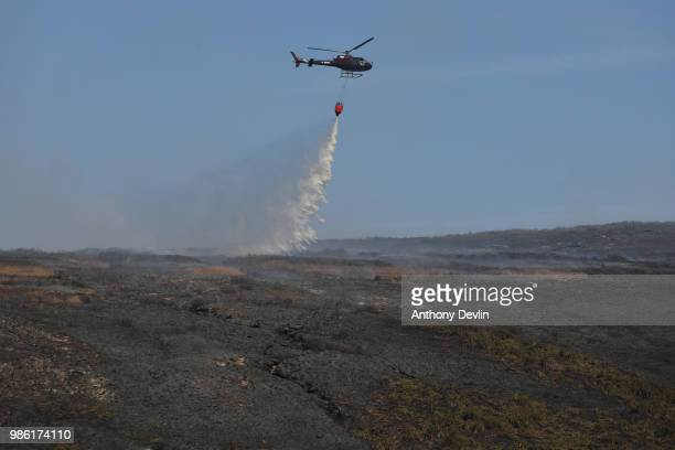 A helicopter drops water on smouldering moorland as wildfires continue to burn on the moors on June 28 2018 in Stalybridge England Around 100...