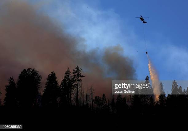 A helicopter drops water on the Camp Fire as it burns in the hills on November 11 2018 near Cresta California Fueled by high winds and low humidity...