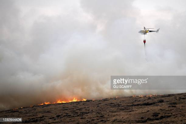 Helicopter drops water, taken from a nearby Reservoir, onto the flames after a resurgence of the moor fire on Marsden Moor, near Huddersfield in...