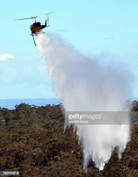 A helicopter drops water to douse a fire approaching houses in the Faulconbridge area of the Blue Mountains on October 24 2013 Thousands of largely...
