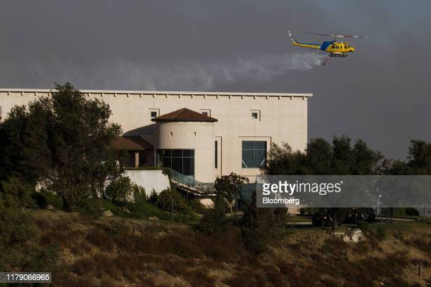 A helicopter drops water to protect the Ronald Reagan Presidential Library during the Easy Fire in Simi Valley California US on Wednesday Oct 30 2019...
