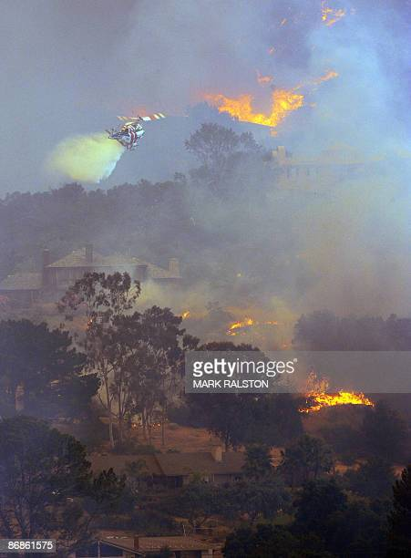 Helicopter dumps water onto flames as houses burn and others are threatened by flames during the Jesusita Fire in the hills of Santa Barbara, May 6,...