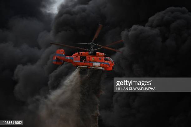 Helicopter dumps water onto the site of an explosion and fire at a plastics factory on the outskirts of Bangkok on July 5, 2021.