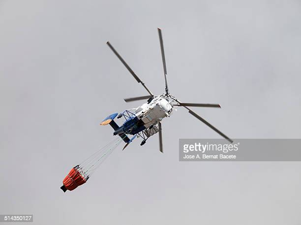 helicopter fire with water hanging basket - helicopter rotors stock photos and pictures
