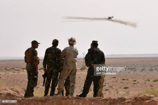 TOPSHOT A helicopter fires rockets as Syrian government forces hold a position in Kobajjep area on the southwestern outskirts of Deir Ezzor on...