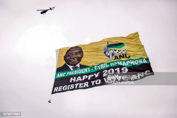A helicopter flies a giant flag from the South African ruling Party African National Congress displaying a picture of South African president Cyril...