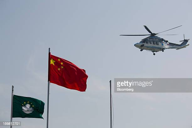 A helicopter flies above a Macau flag left and a People's Republic of China flag outside the ferry terminal in Macau China on Monday Jan 7 2013...