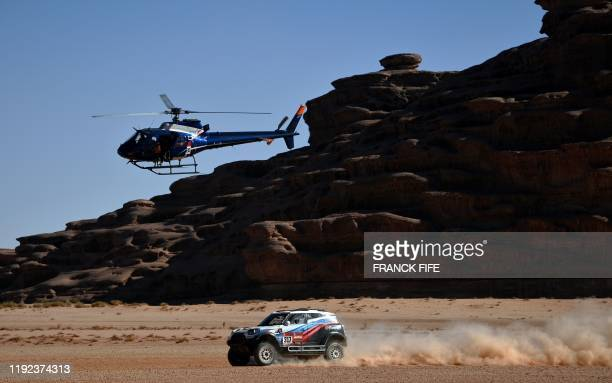 TOPSHOT A helicopter flies as Russia's driver Vladimir Vasilyev and codriver Vitaly Yevtyekhov of Ukrainia steer their Mini during the Stage 3 of the...