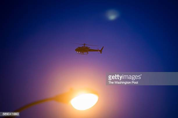 A helicopter flies in circles over the intersection of West North Avenue and Pennsylvania Avenue as protestors walk for Freddie Gray on West North...