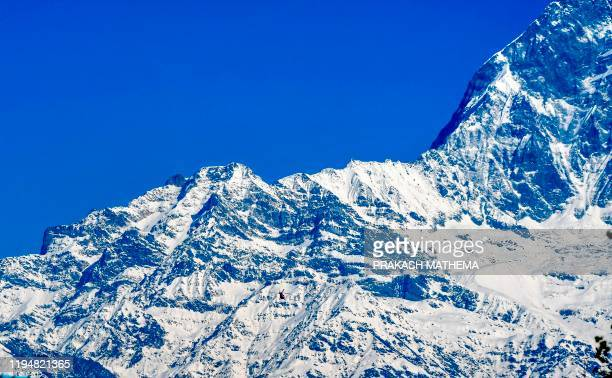 Helicopter flies in front of the Annapurna mountain range, in Pokhara, some 200 kms west of Kathmandu on January 20, 2020. - Rescuers intensified an...
