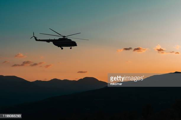 helicopter flies in the mountains at sunset in the dark - helicopter stock pictures, royalty-free photos & images