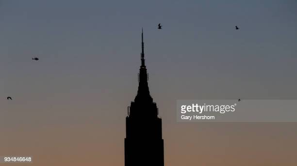 A helicopter flies next to the Empire State Building at sunrise in New York City on March 18 2018 as seen from Hoboken New Jersey