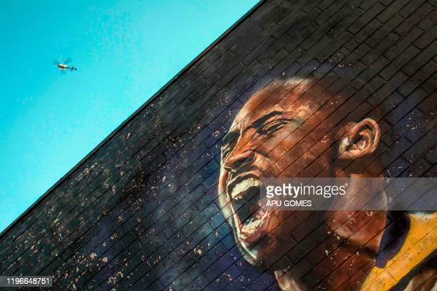TOPSHOT A helicopter flies over a Kobe Bryant mural in downtown Los Angeles on January 26 2020 Nine people were killed in the helicopter crash which...