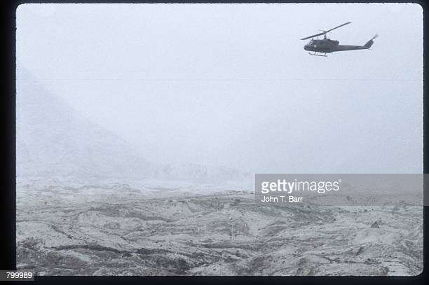 Helicopter flies over an ash covered landscape May 23, 1980 in Washington State. On May 18 an earthquake caused a landslide on Mount St. Helens''...