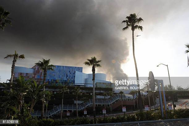 A helicopter flies over burning structures at Universal Studios in Universal City California on June 01 2008 More than 100 firefighters were battling...
