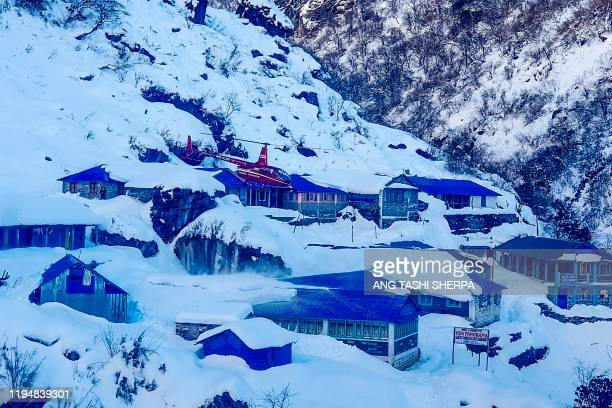 Helicopter flies over Deurali near the avalanche site in Annapurna mountain region, some 200 kms west of Kathmandu on January 20, 2020. - Rescuers...