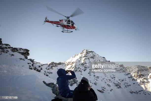 A helicopter flies over skiers on the Bec de Rosses mountain prior to the Xtreme Freeride World Tour final on the Bec de Rosses mountain on March 23...