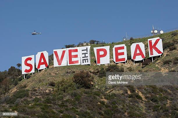 A helicopter flies over the iconic 450footlong Hollywood sign after activists covered it with banners during an effort to prevent the building of...