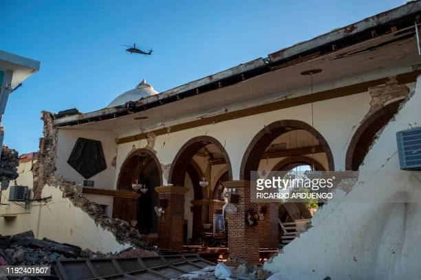 A helicopter flies over the Inmaculada Concepcion church built in 1841 seen partially collapsed after an earthquake hit the island in Guayanilla...
