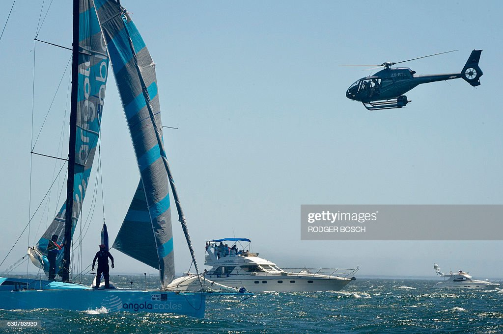 A Helicopter Flies Over Yachts As They Sail Out Of Table Bay At The